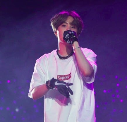 Suga raps into a microphone during a concert