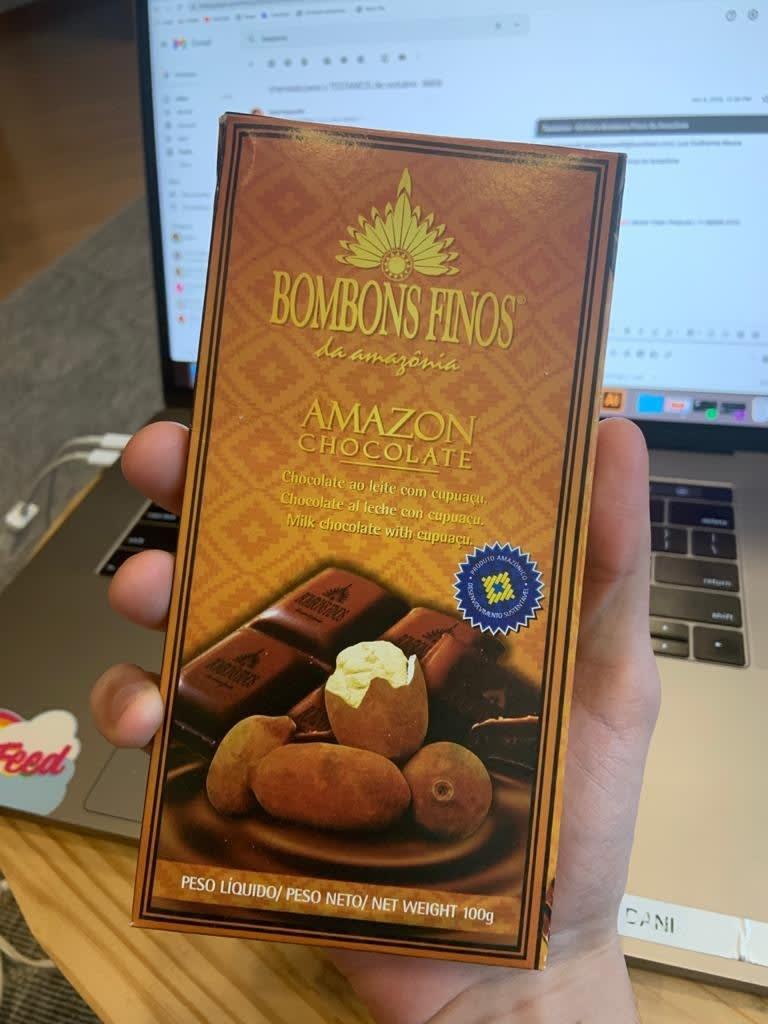 Uma mão segura a caixa dos bombons em frente a um notebook. A caixa tem cor marrom clara e mostra tanto uma imagem de chocolate quanto dos ingredientes.