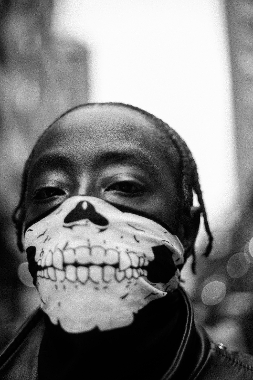 Homem jovem negro usando máscara preta com estampa de caveira.