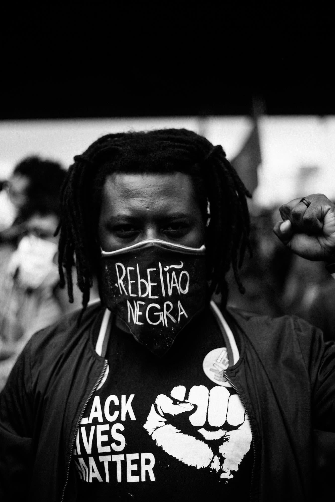 Homem negro de dreadlocks curtos com punho levantado, camiseta Black Lives Matter e máscara com os dizeres REBELIAO NEGRA.