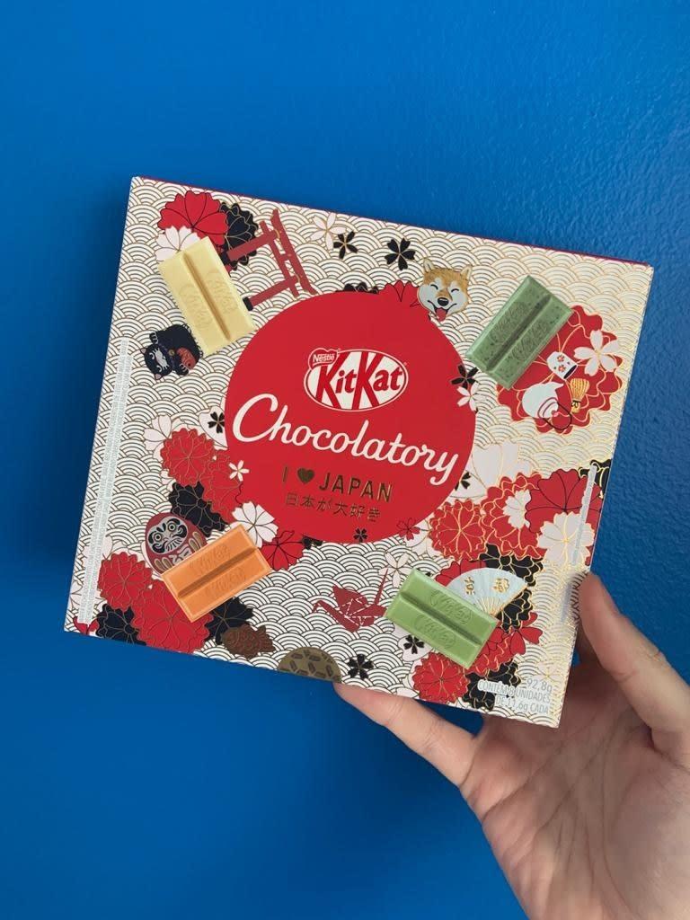 Uma mão segura a caixa do produto na frente de um fundo azul. A embalagem é toda desenhada com temática japonesa e mostra os quatro sabores do chocolate em destaque, cada um de uma cor diferente.