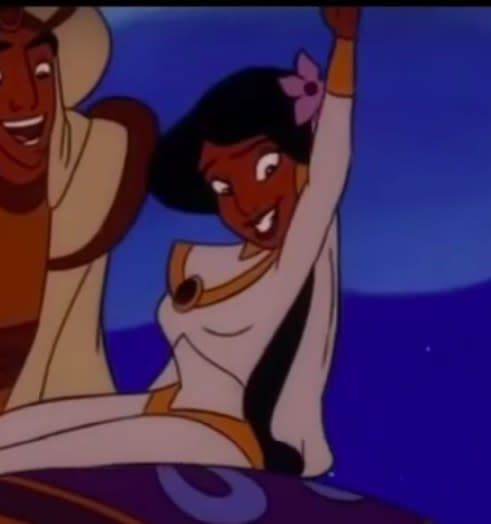 Jasmine wears a wedding outfit and waves