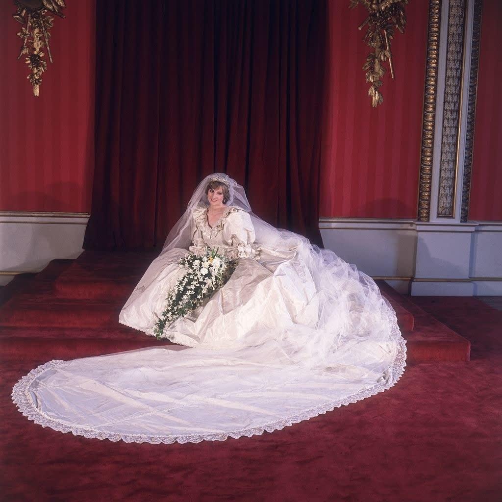 Princesa Diana vestida de noiva e sentada no chão, posando para a foto