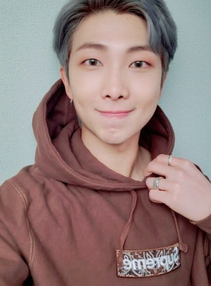 Rm looks at the camera and smiles; his hair is grey; his hand touches the neck of his hoodie