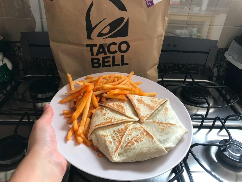 Foto do Triple Crunchwrap em um prato, com batatas fritas ao lado. Na frnete do prato está uma sacola de papel com o logo do Taco Bell.