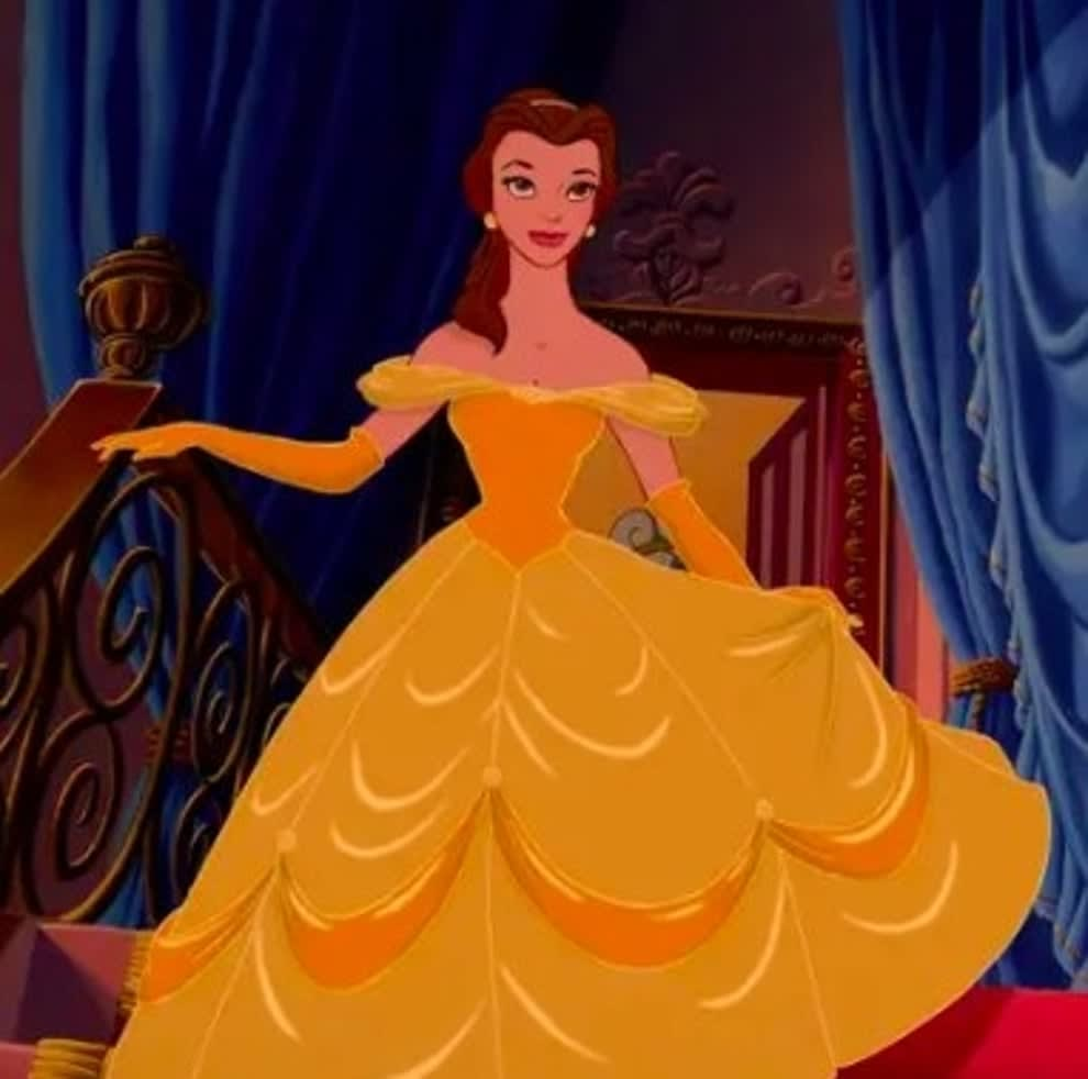 Belle walks down the stairs in a gold ballgown
