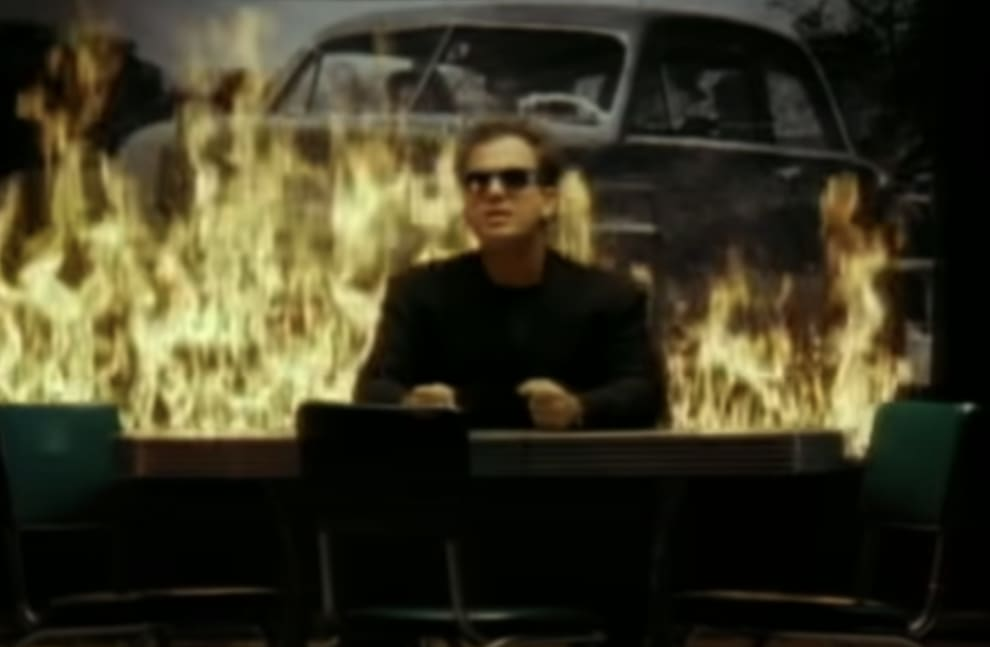 Billy performing the song at a piano with fire behind him in the music video