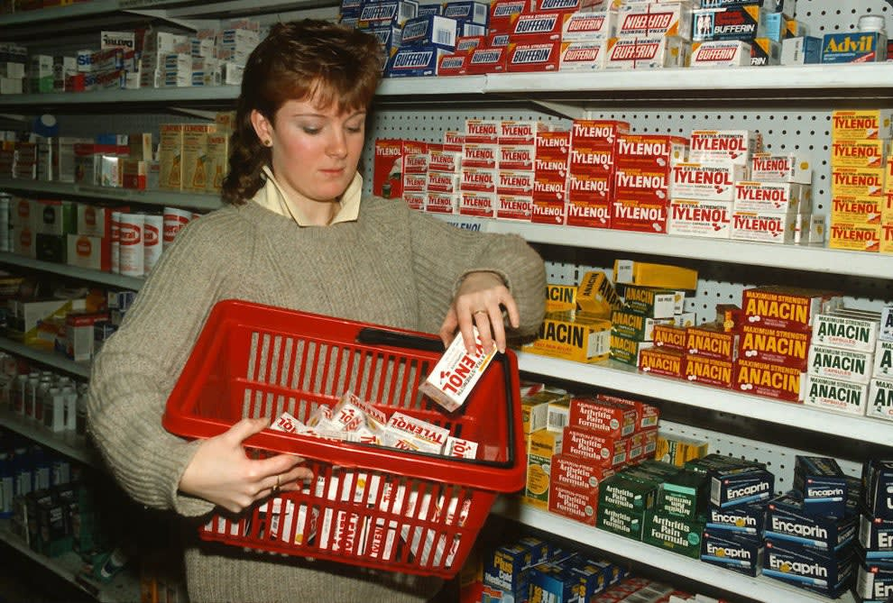 A woman removing tylenol from the shelf