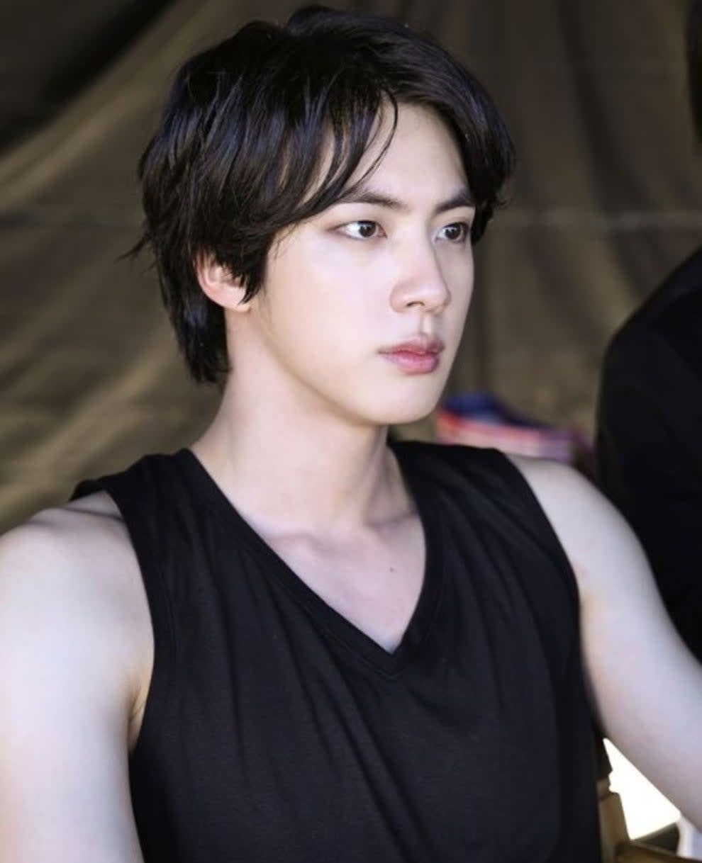 Jin wears a black tank top and looks away from the camera; he has dark hair