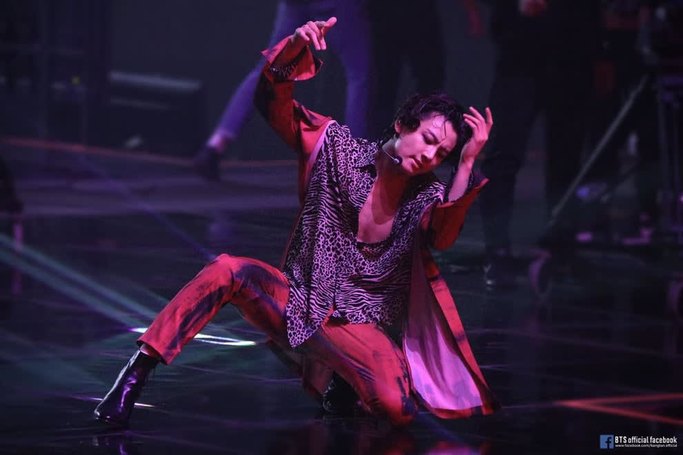 Jungkook performs My Time; he is performing a dance move that involves kneeling on the ground with his hands in the air; he has long dark hair