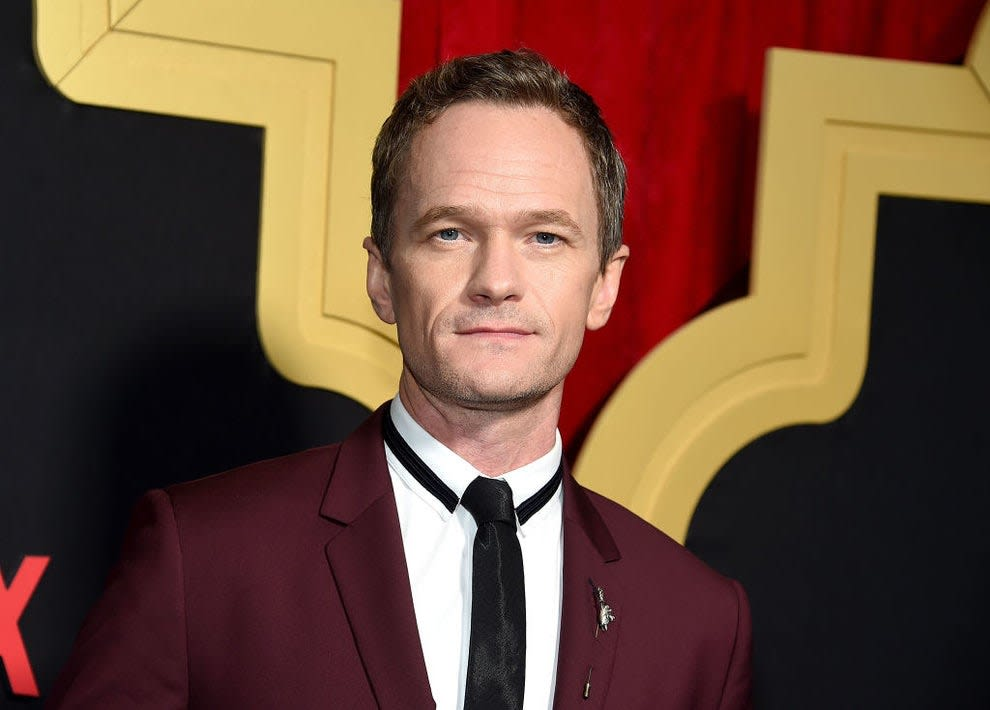 Neil Patrick Harris posing at an event in a dark suit