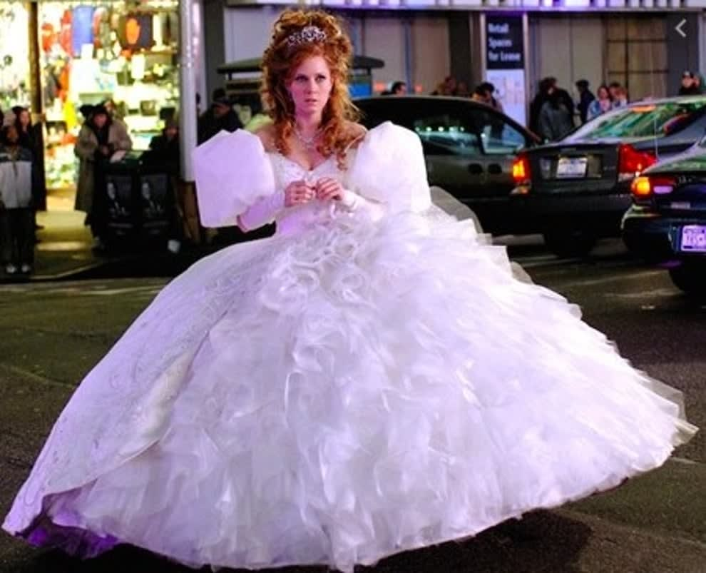 A live-action Giselle stands in the street in a huge puffy dress