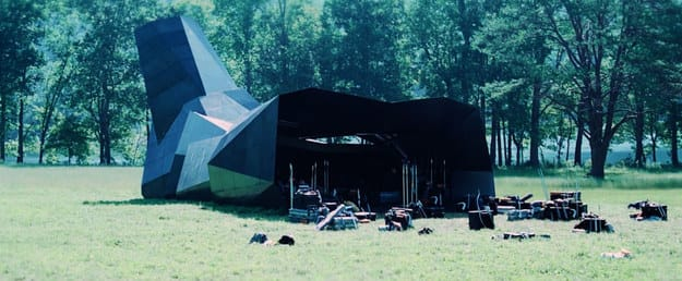 A metal cornucopia structure in a field with bags of miscellaneous materials scattered about
