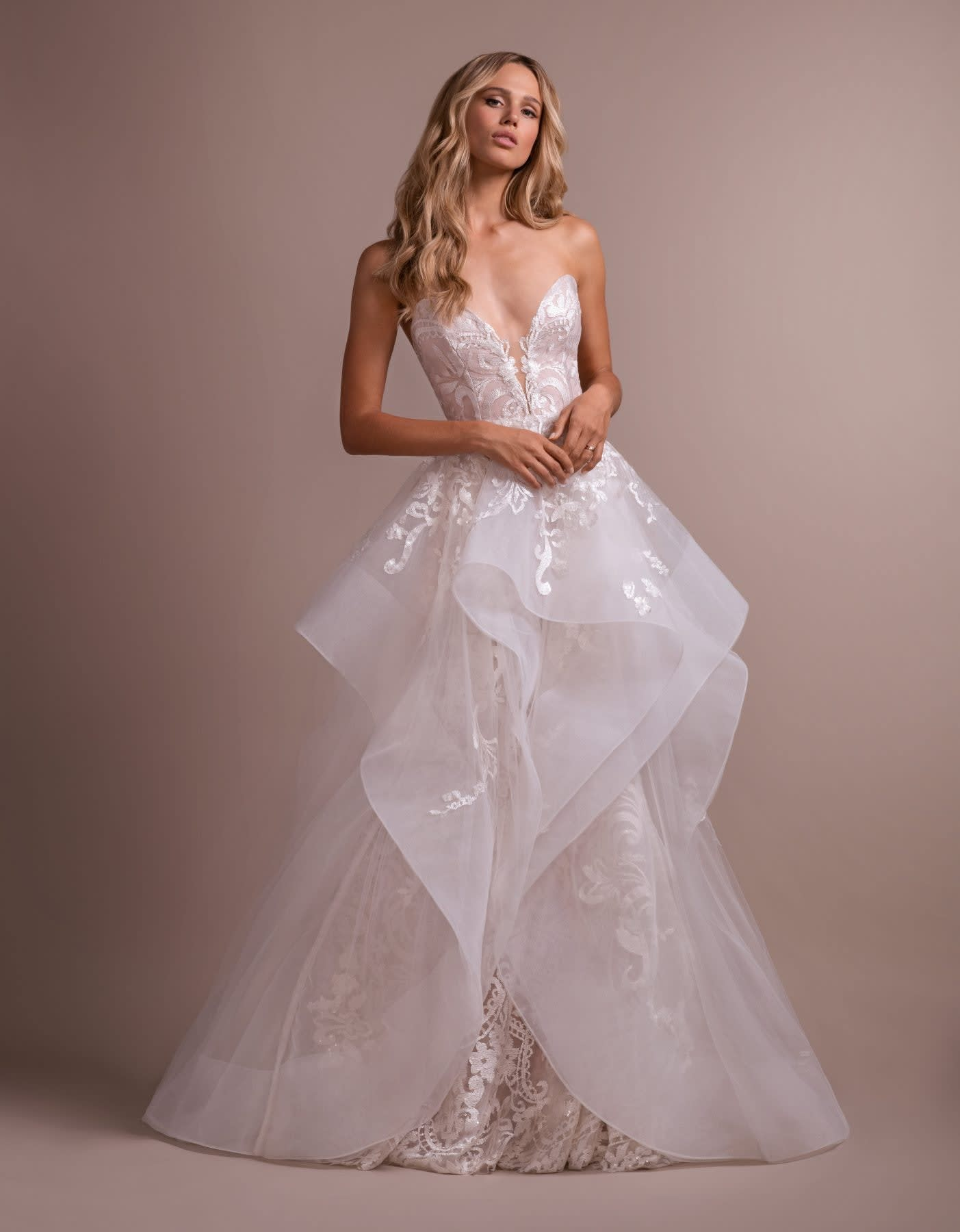 A sweetheart, strapless gown with a lacy underlay and flowy overskirt