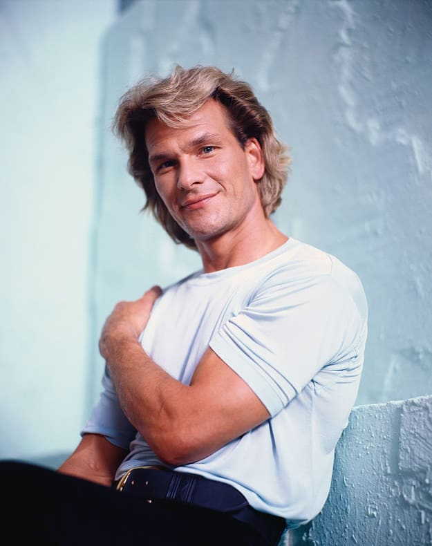 Famous man from the '80s wearing a t-shirt and slacks, light, long hair, while putting his arm on his shoulder
