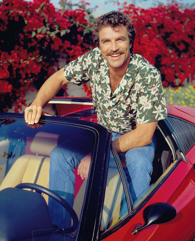 Famous man from the '80s sitting on the roof of his convertible, wearing a tropical shirt, and smiling with a mustache