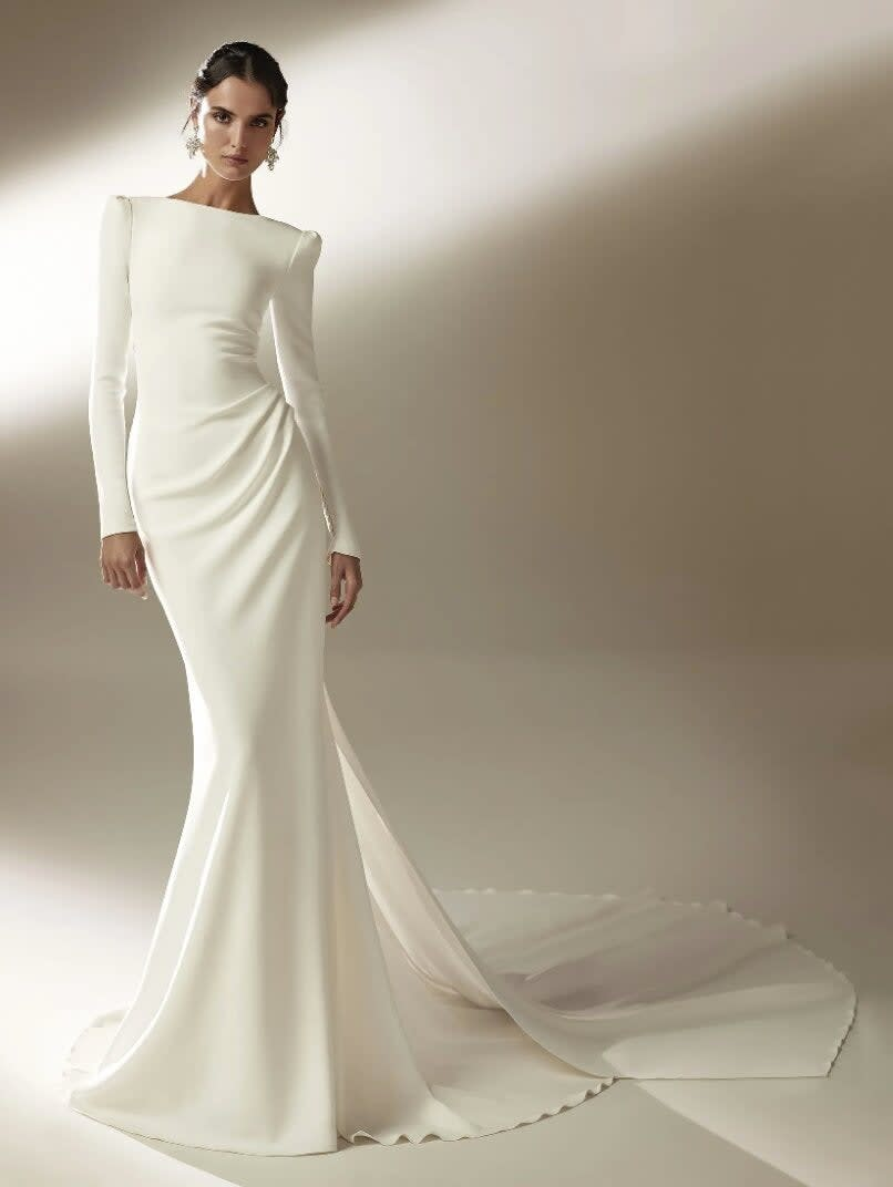 A mermaid gown with a bateau neckline and long sleeves