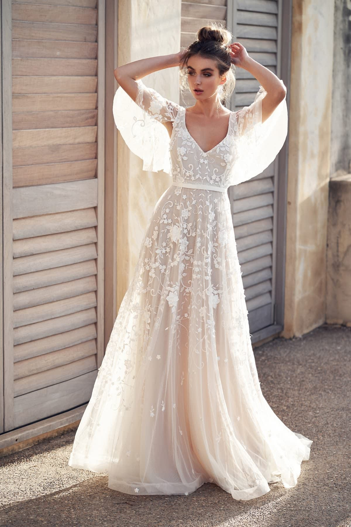A v-neck , a-line gown with a floral lacy overlay and draped sleeves