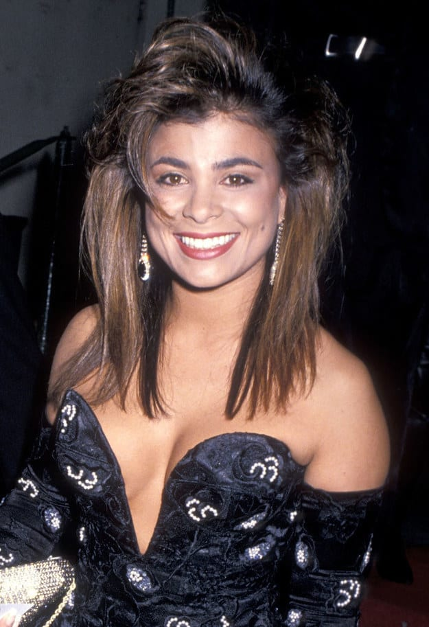 Famous woman from the late '80s wearing a dark, glittered dress, teased hair, and a smile