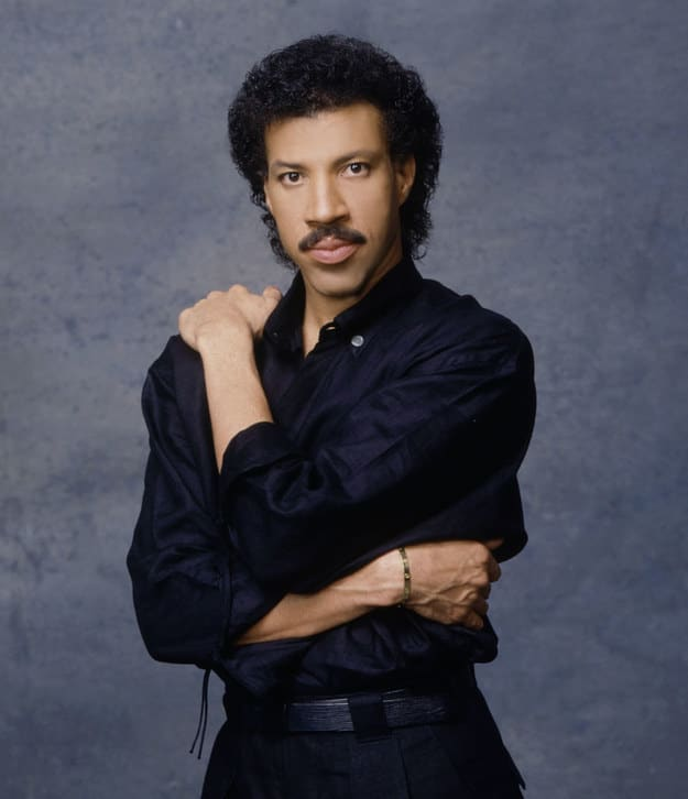 Famous man from the '80s with a mustache and dark hair posing for a portrait with his arms crossed