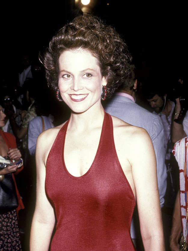 A famous woman from the '80s with short, curly hair, smiling, and wearing a halter dress on a red carpet