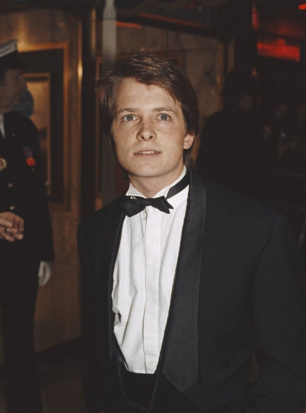 Famous man from the '80s wearing a suit and bowtie at a red carpet event, short, light, short hair