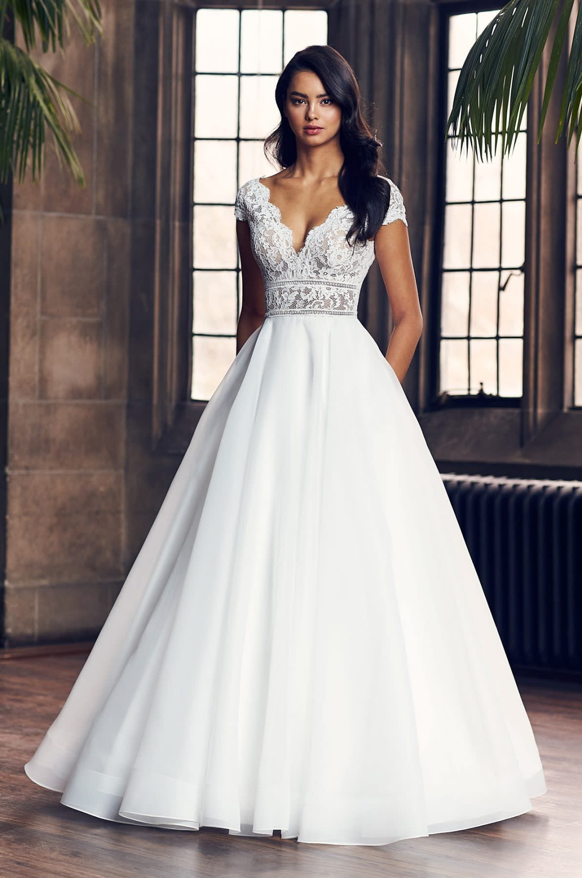 A cap sleeve ball gown with a lacy top and a flowing skirt