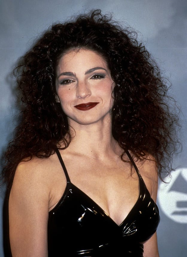 Famous woman from the '80s with dark, teased, curly hair, wearing makeup, and a latex dress at the Grammys