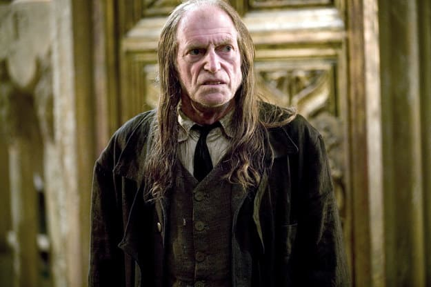 Old man with black, gruffy suit and beard and long hair