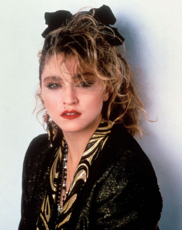 Famous woman from the '80s wearing lipstick, dangly earrings, loud clothing, teased hair, and a bow