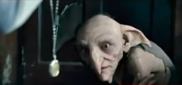 nervous looking house elf peering at a gold chain