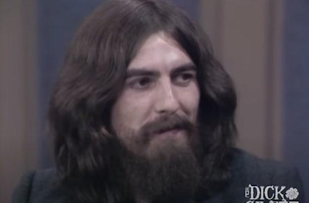 Um membro dos Beatles com o cabelo comprido e uma barba longa é entrevistado.