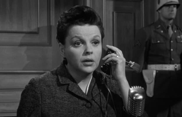 Uma foto preto e branca de 1961 que mostra uma mulher falando no telefone enquanto está na frente de um juiz.