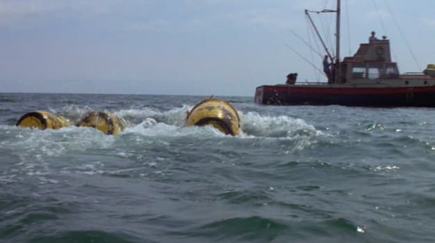 Three yellow barrels floating in the rough water of the ocean with a boat in the distance