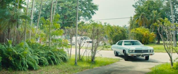 A blue car driving up a driveway in Miami, FL