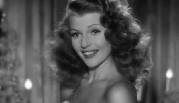 Uma imagem em preto e branco da cena do filme onde um ator pergunta se ela está vestida e ela joga o cabelo de forma sensual.