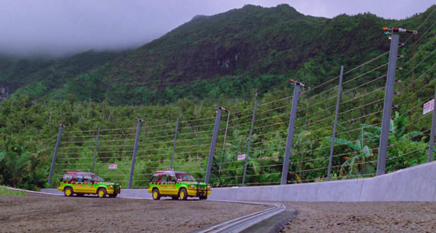 Two brightly colored jeeps driving through a gated, tropical landscape