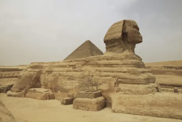 A giant man-made statue next to a pyramid