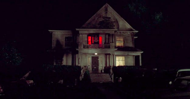 A run-down frat house with red lights on upstairs and cars scattered in the lawn