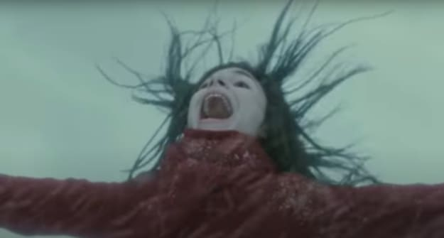 girl with dark hair blowing in wind while screaming