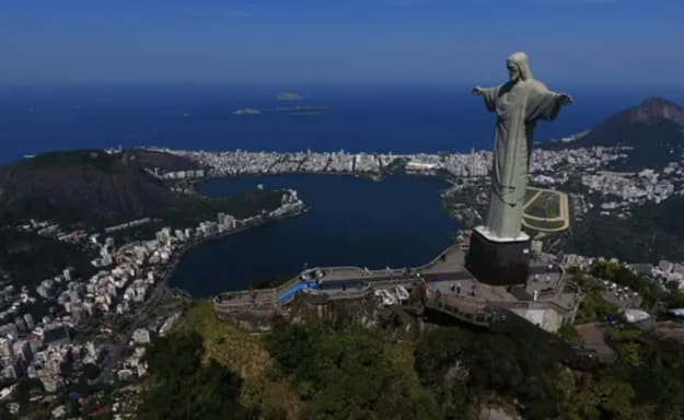 A giant statue of Christ with his arms spread out, overlooking a city
