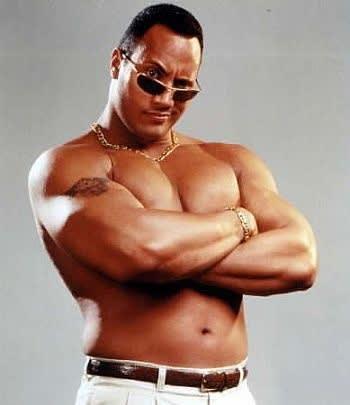 Dwayne jovem, de braços cruzados, tampando os peitos