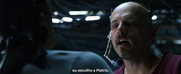 """Captura de tela de cena do filme, com o personagem Cypher à direita dizendo que """"escolhe a Matrix""""."""