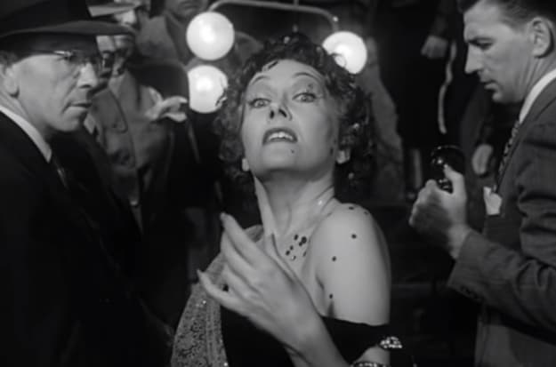Uma mulher mais velha toda produzida andando em direção à câmera em um filme preto e branco.