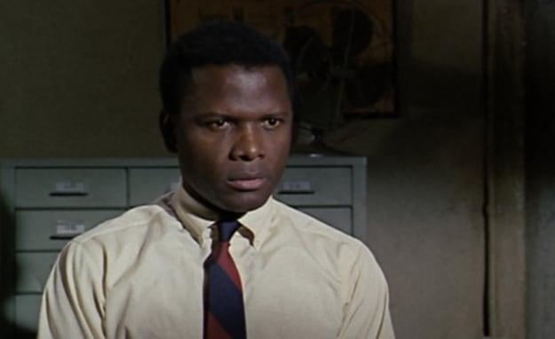 Uma imagem colorida de um filme dos anos 60 no qual um homem de camisa e gravata está sentado em uma delegacia.