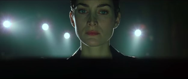 """Captura de tela de cena do filme """"Matrix"""", com o rosto da personagem Trinity ao centro"""