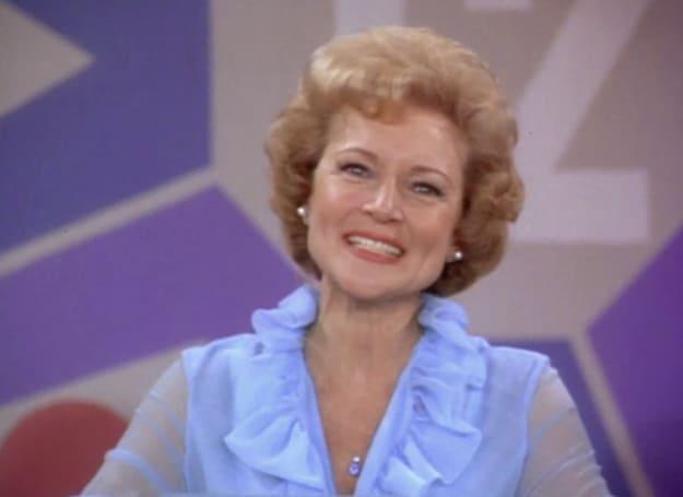 """Uma mulher no programa """"Password"""" (Senha) com um cabelo no estilo dos anos 70 e uma blusa azul."""
