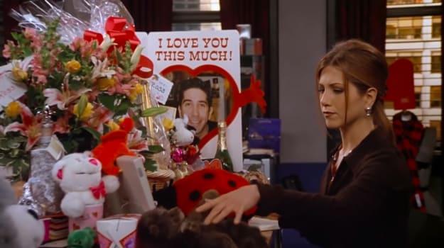 """Rachel olha para a sua mesa cheia de presentes de Ross, incluindo um cartão com seu rosto dizendo """"Meu amor por você é grande assim!"""""""
