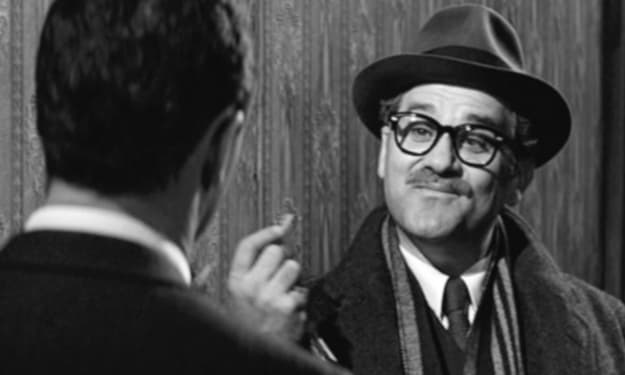 Uma imagem em preto e branco de um homem de bigode, óculos e chapéu fazendo uma consulta na casa de um paciente.
