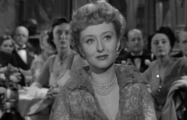 """Uma atriz famosa usando um colar e uma roupa de gala de 1950 no filme """"A Malvada""""."""